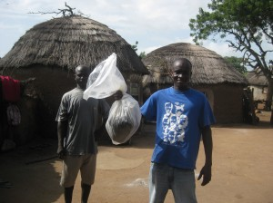 Peter taking home a gift from Hawa (one of the women who work at the Nymaliga water treatment center) and her family - a big bag of groundnuts (peanuts!)