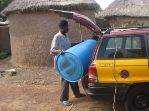 Loading a blue tub into the trunk outside of Fati's house