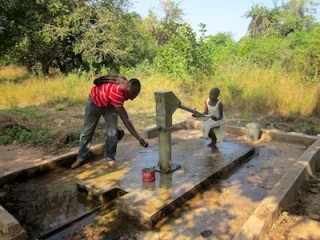 Shak tastes the borehole water in Buhijaa