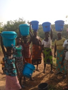 Happy customers on their way home with full buckets of clean drinking water