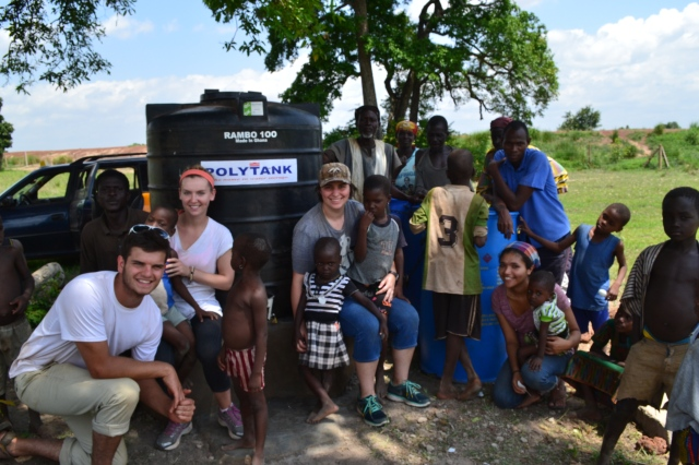 Team Sharifa (Katie, Lucas, Stephanie & Sandra) post with their women entrepenuers and some kiddos in front of Namdu's up and running water treatment center