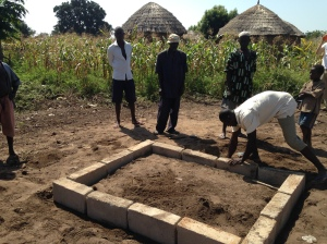 The village mason and his team constructing the foundation.