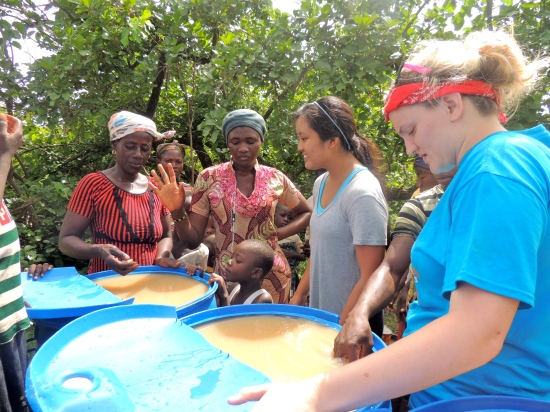 Haley and Caroline teach Bellamina and Damu how to use alum to remove the turbidity from the water.