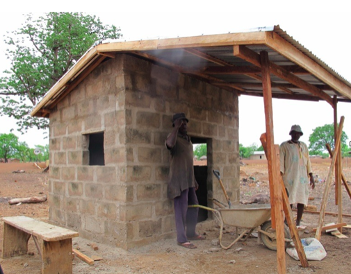 The community helps us add the last cement bricks to the foundation.